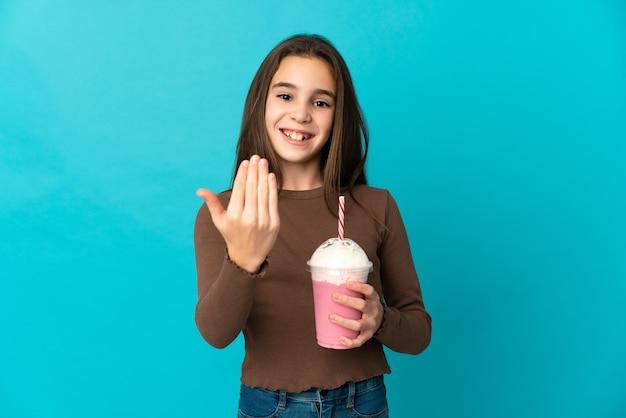 Bambina con frappè alla fragola isolato su priorità bassa blu che invita a venire con la mano. felice che tu sia venuto
