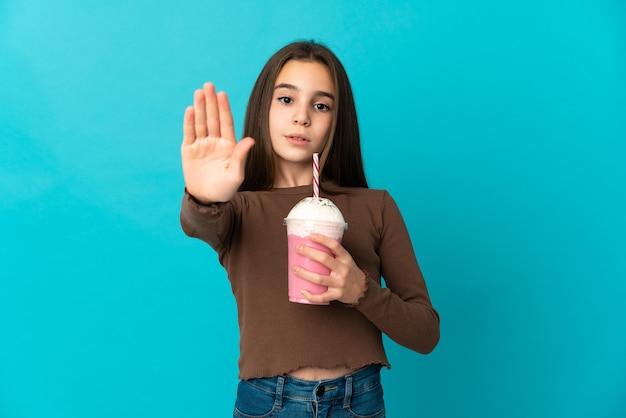 Bambina con frappè alla fragola isolato su priorità bassa blu che fa gesto di arresto