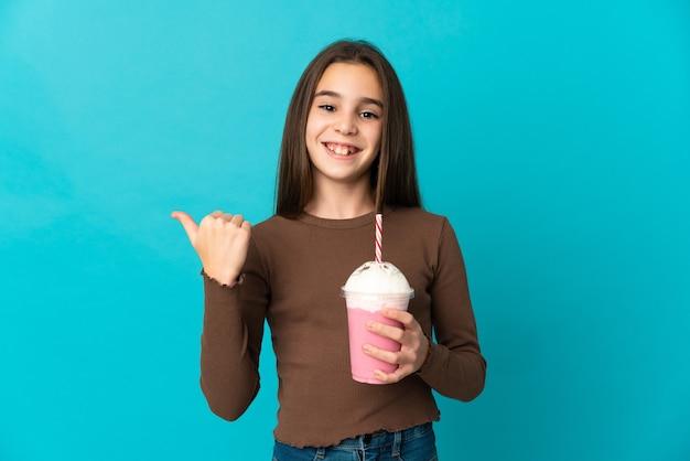 Bambina con frappè alla fragola isolato su sfondo blu che punta di lato per presentare un prodotto