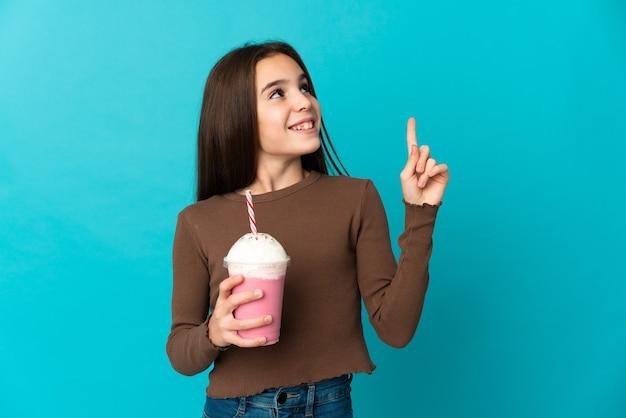 Bambina con frappè alla fragola isolato su sfondo blu rivolto verso l'alto una grande idea