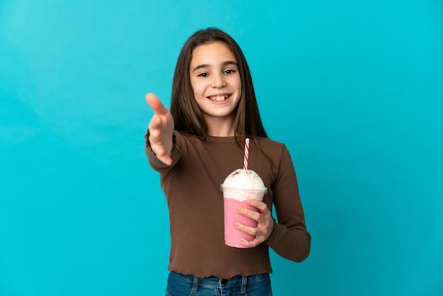 Bambina con frappè alla fragola isolato su sfondo blu stringe la mano per chiudere un buon affare