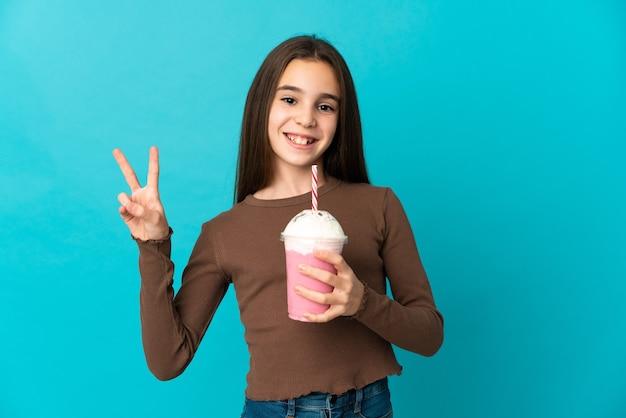 Bambina con milkshake alla fragola isolato su sfondo blu sorridente e mostrando segno di vittoria