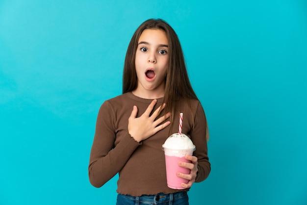 Bambina con frappè alla fragola isolato su sfondo blu sorpreso e scioccato mentre guarda a destra