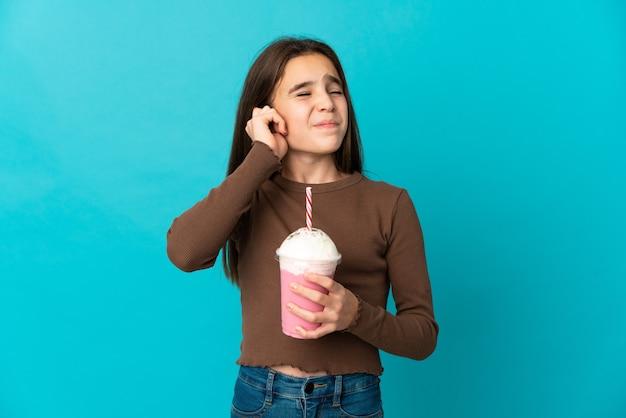 Bambina con frappè alla fragola isolato sulla parete blu frustrata e che copre le orecchie