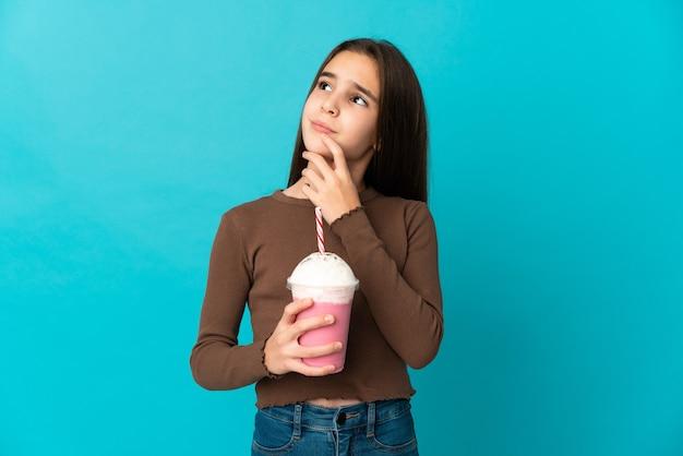 Bambina con frappè alla fragola isolato sulla parete blu che ha dubbi mentre osserva in su