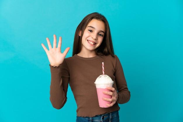 Bambina con frappè alla fragola isolato sulla parete blu che saluta con la mano con l'espressione felice