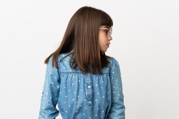 Bambina con gli occhiali da sole isolati su fondo bianco che guarda al lato