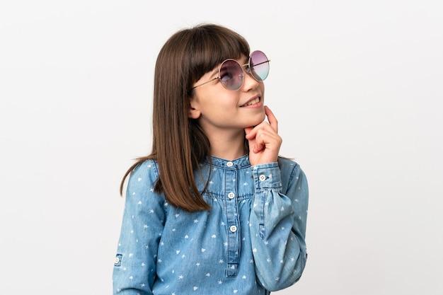 Bambina con occhiali da sole isolati su sfondo bianco pensando a un'idea mentre guarda in alto