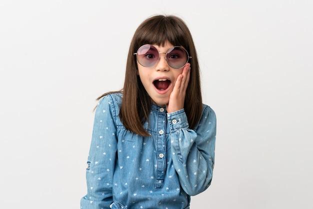 Bambina con gli occhiali da sole isolati sul muro bianco con espressione facciale sorpresa e scioccata