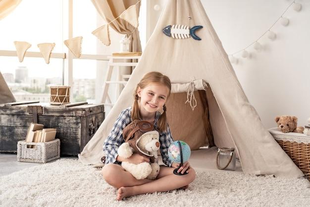 La bambina con l'orsacchiotto e il globo che si siede nel wigwam si è sistemata nella stanza dei giochi