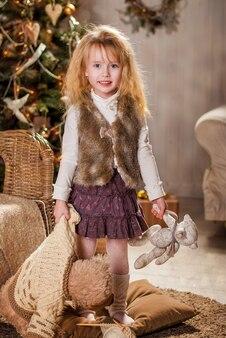 Una bambina con orsacchiotti in mano sta vicino all'albero di natale.
