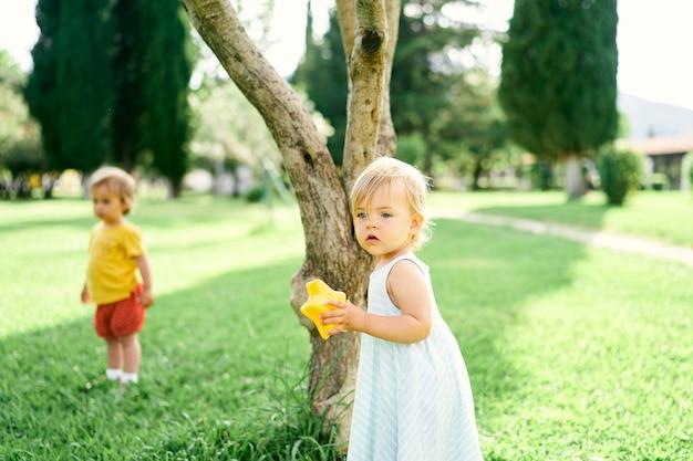 La bambina con un giocattolo in mano sta vicino a un albero nel parco sullo sfondo di un altro