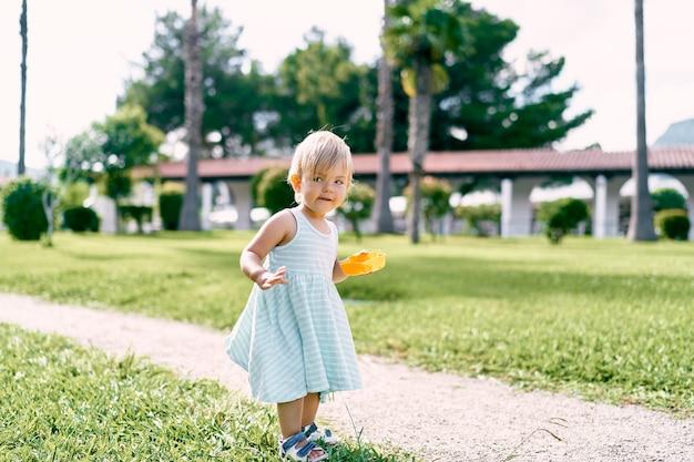 La bambina con un giocattolo in mano sta sul sentiero sul prato mezzo voltata