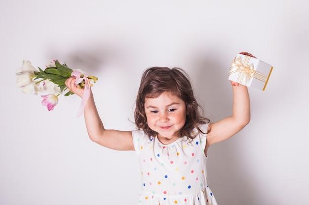Bambina con tulipani e scatola con regalo per la mamma