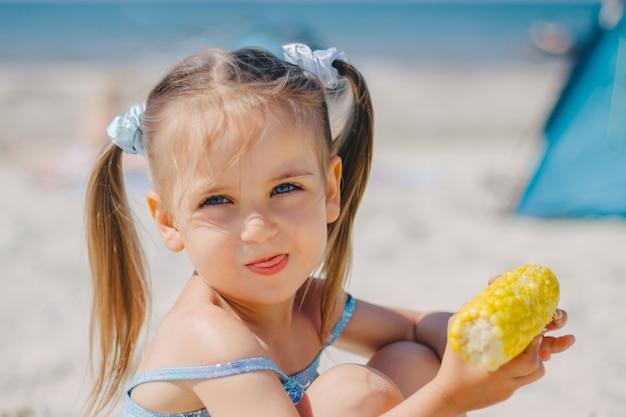 La bambina con due code in costume da bagno a sirena sulla spiaggia del mare mangia il mais