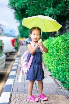 Bambina con ombrello e zaino a piedi nel parco pronto a tornare a scuola nel piovere giorno
