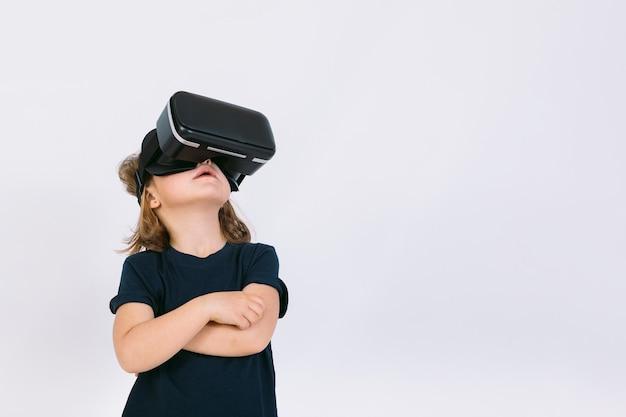 Bambina con occhiali per realtà virtuale, alzando lo sguardo su sfondo bianco