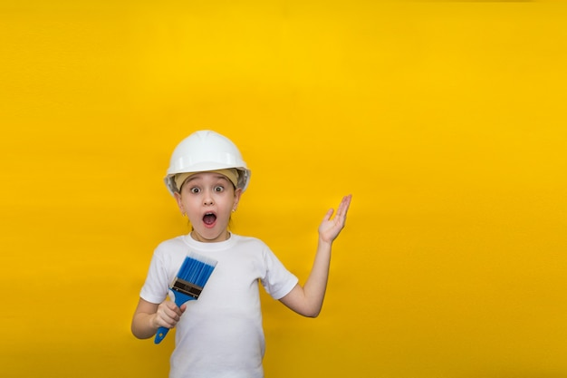 La bambina con gli occhi spalancati e la bocca in un casco della costruzione tiene un pennello