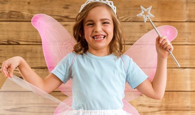 Bambina con ali e bacchetta magica.
