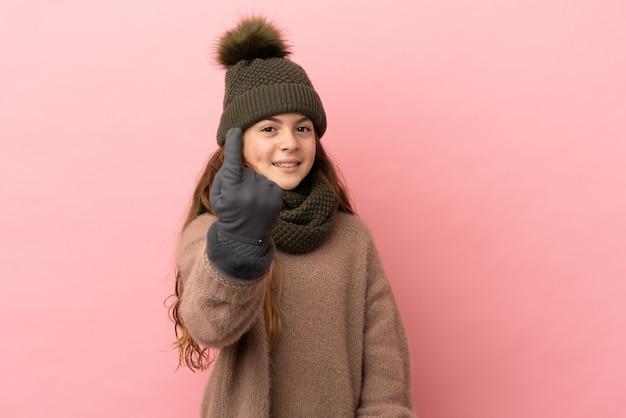 Bambina con cappello invernale isolato su sfondo rosa facendo gesto venuta