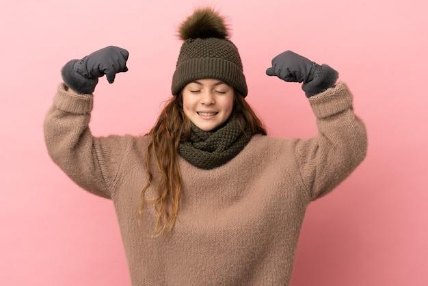 Bambina con cappello invernale isolato su sfondo rosa che fa un gesto forte