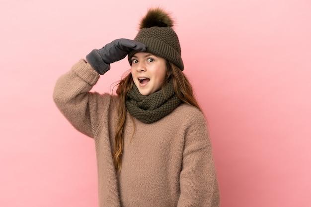 Bambina con cappello invernale isolato su sfondo rosa che fa un gesto a sorpresa mentre guarda di lato