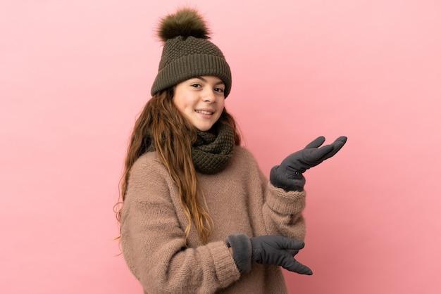 Bambina con cappello invernale isolato su sfondo rosa che allunga le mani di lato per invitare a venire
