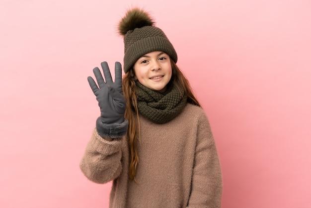 Bambina con cappello invernale isolato su sfondo rosa felice e contando quattro con le dita