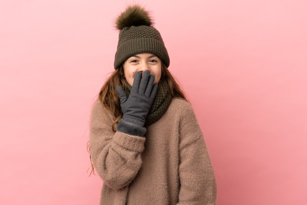 Bambina con cappello invernale isolato su sfondo rosa felice e sorridente che copre la bocca con la mano