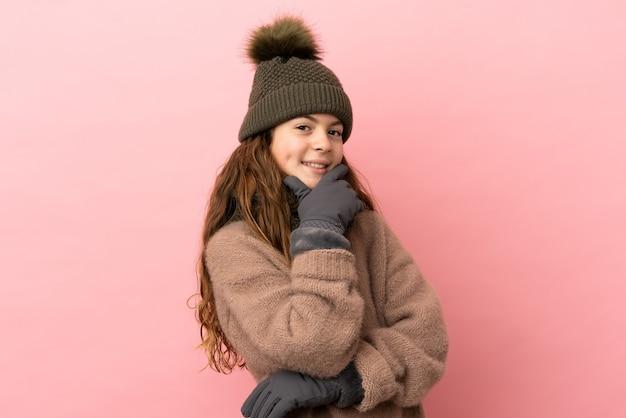 Bambina con cappello invernale isolato su sfondo rosa felice e sorridente