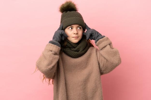 Bambina con cappello invernale isolato su sfondo rosa con dubbi e pensieri