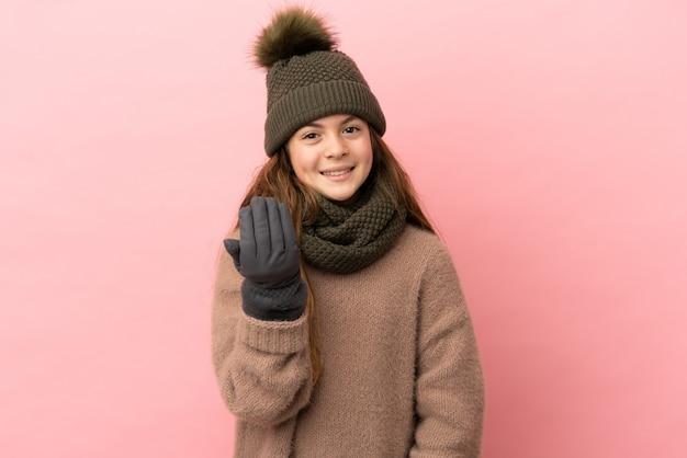 Bambina con cappello invernale isolato su sfondo rosa che invita a venire con la mano. felice che tu sia venuto