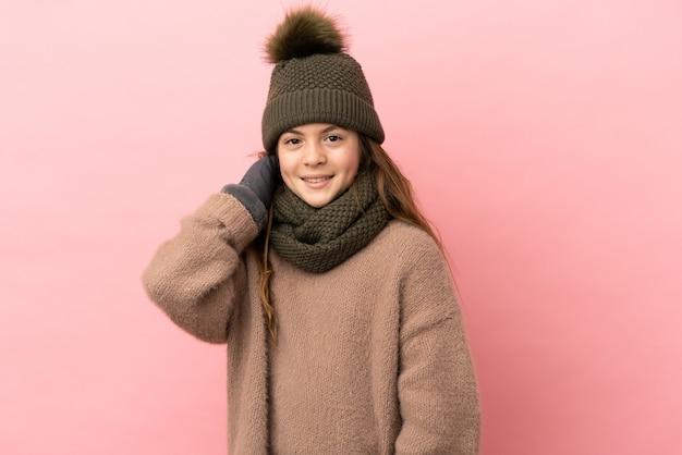 Bambina con cappello invernale isolato su sfondo rosa ridendo