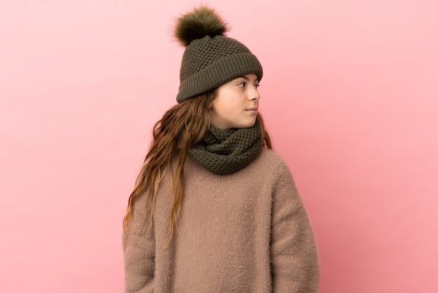 Bambina con cappello invernale isolato su sfondo rosa guardando di lato