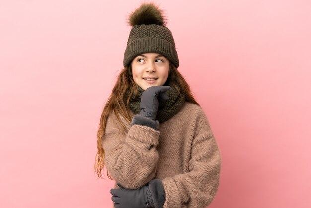 Bambina con cappello invernale isolato su sfondo rosa e alzando lo sguardo
