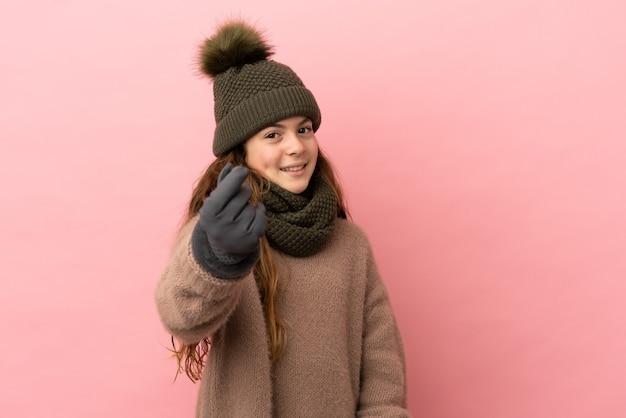 Bambina con cappello invernale isolato su sfondo rosa che fa gesto di denaro