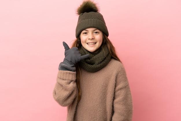 Bambina con cappello invernale isolato su sfondo rosa che fa gesto di telefono. richiamami segno
