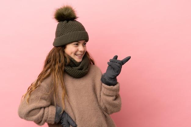 Bambina con cappello invernale isolato su sfondo rosa che punta il dito di lato e presenta un prodotto