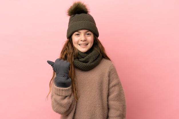 Bambina con cappello invernale isolato su sfondo rosa che punta al lato per presentare un prodotto