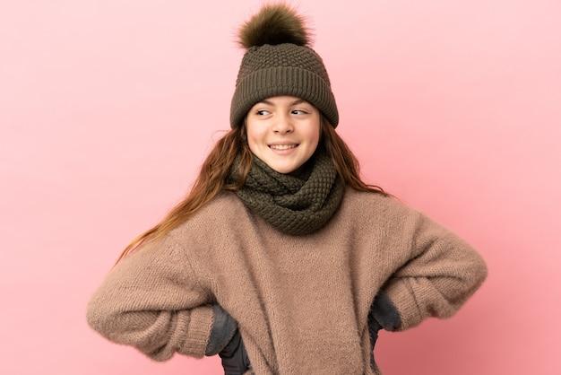 Bambina con cappello invernale isolato su sfondo rosa in posa con le braccia all'anca e sorridente