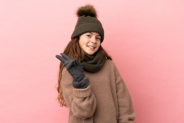 Bambina con cappello invernale isolato su sfondo rosa sorridente e mostrando segno di vittoria