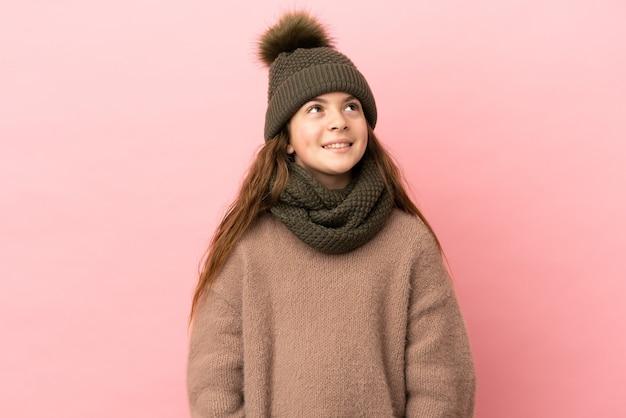 Bambina con cappello invernale isolato su sfondo rosa pensando a un'idea mentre guarda in alto