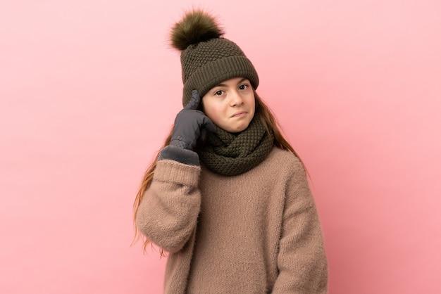 Bambina con cappello invernale isolato su sfondo rosa pensando a un'idea