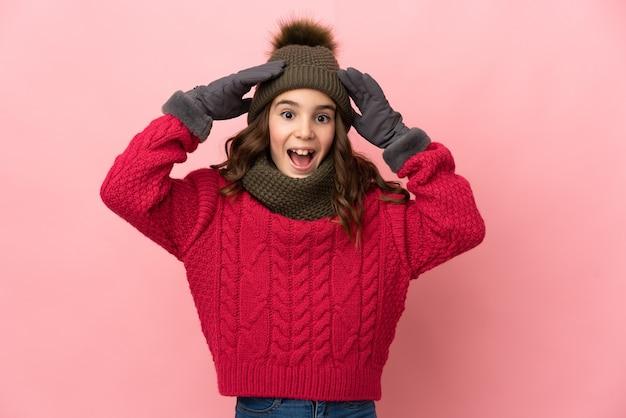 Bambina con cappello invernale isolato su sfondo rosa con espressione sorpresa