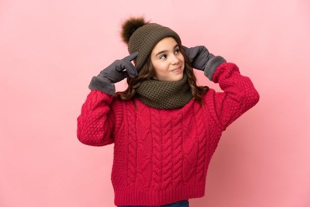 Bambina con cappello invernale isolato sulla parete rosa avendo dubbi e pensando