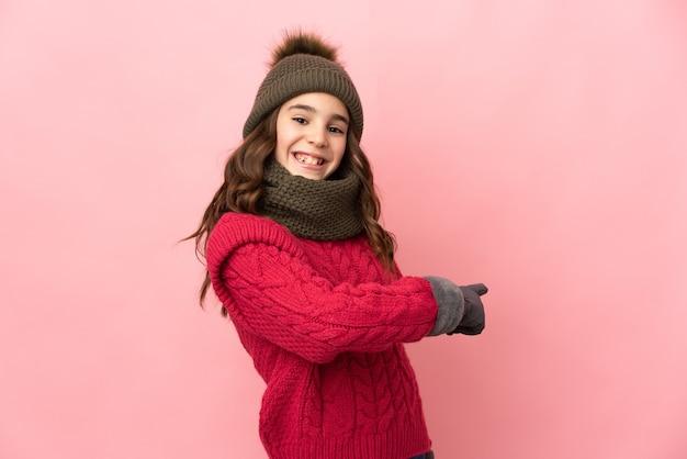 Bambina con cappello invernale isolato sulla parete rosa che punta indietro