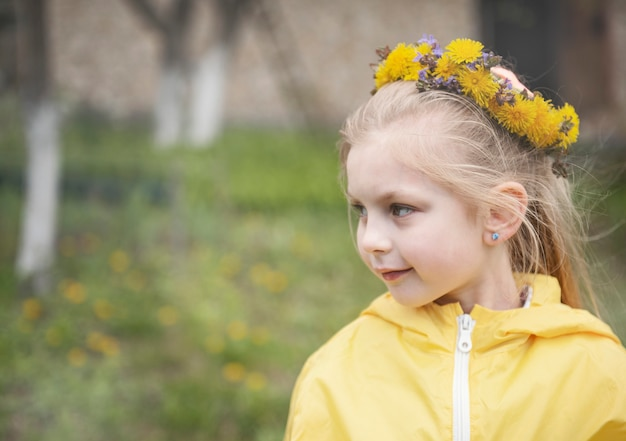 Bambina con una ghirlanda di denti di leone gialli in testa