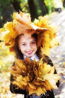 Bambina con foglie gialle