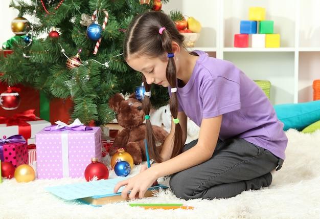 Bambina che scrive una lettera a babbo natale vicino all'albero di natale