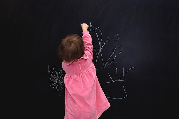 Bambina che scrive qualcosa sulla lavagna
